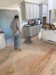 Worker sanding hardwood floors